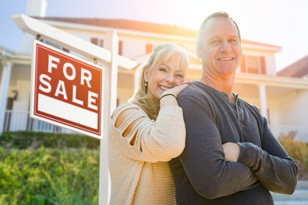 Older couple standing in front of a house for sale